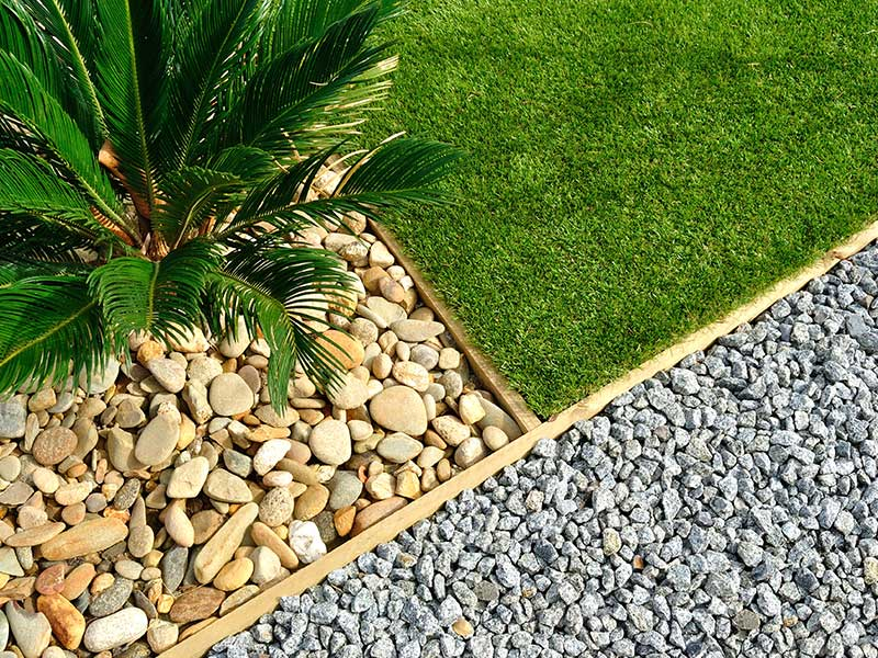 The juxtaposition of grass, rocks, and pebbles as the landscape set the tone of the new custom home