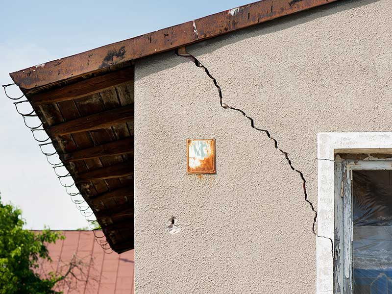 A crack in the wall of the house indicating possible foundation damage