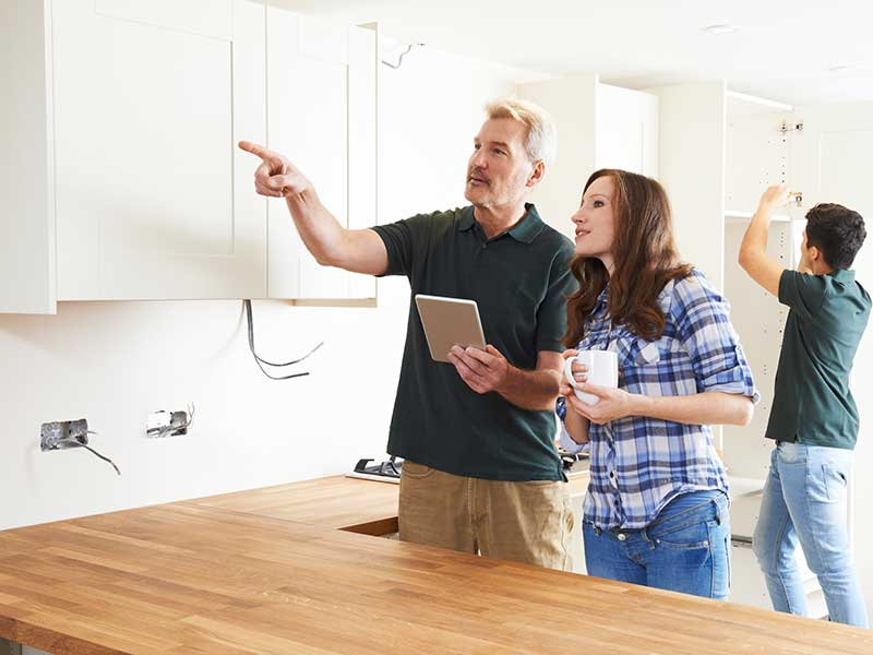 A couple inspecting their new home with the help of a professional to identify defects before moving in