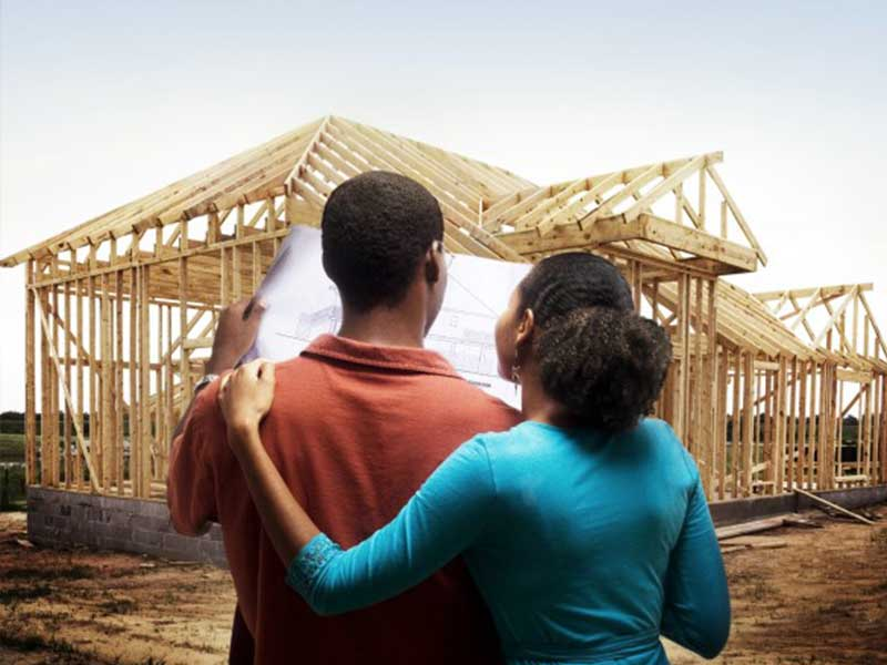 A couple looking at their new house under construction and matching it with the design.