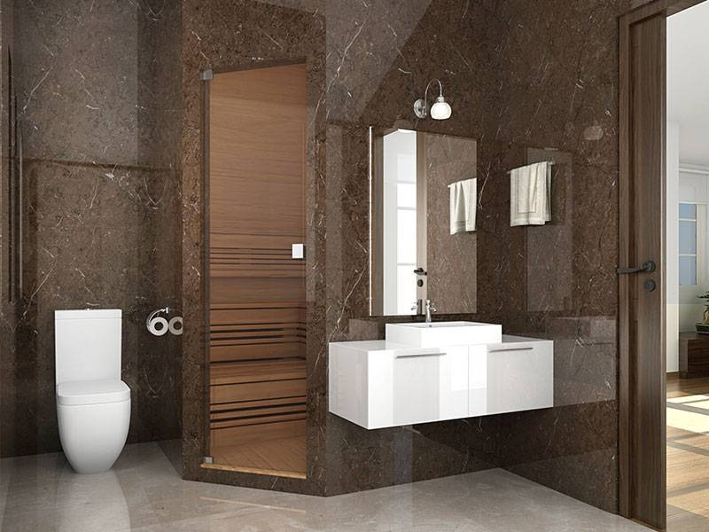 A refurbished bathroom with  white vitrified flooring, dark brown granite wall housing an enclosed bathing area a basin with a mirror to the right and a toilet to the left.