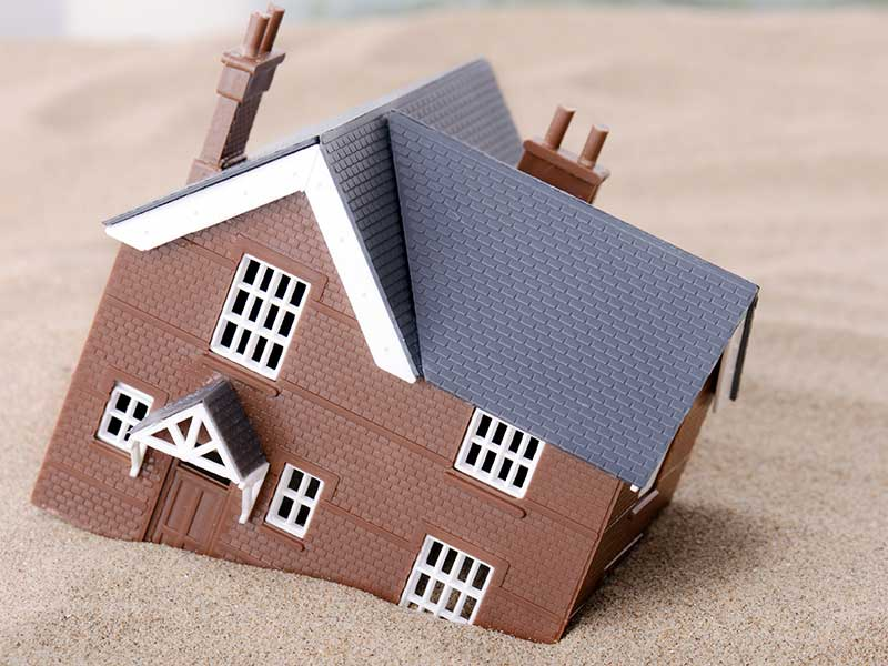Representative picture showing a toy house model sinking in sand