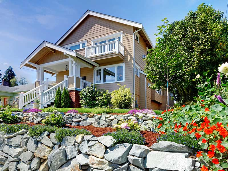 A wide low angle of exterior of a house adorned by a garden with flowering plants that is situated at a height upon raised area which can lead to sliding due to erosion.