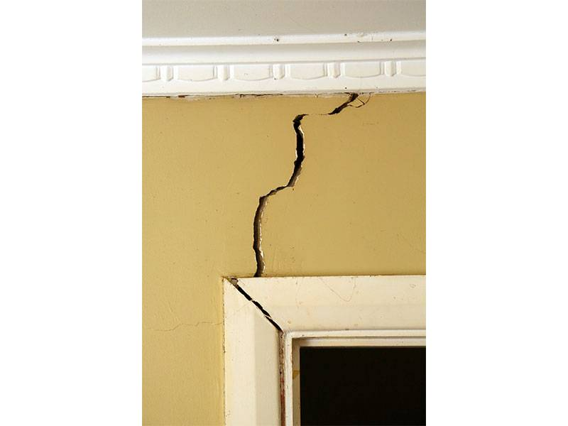 A crack in the foundation wall above a door frame corner extending towards the ceiling which can be sign of problems with the foundation