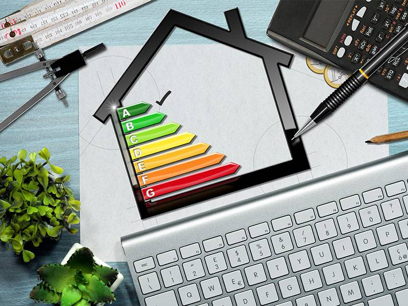 Picture showing a diagramatic representation of a house with energy labels from A to G in increasing order of energy consumption at the center with a tick on A the most energy efficient level, surrounded by measuring instruments and keyboard representing brainstormimg of ideas to make the house more energy efficient.
