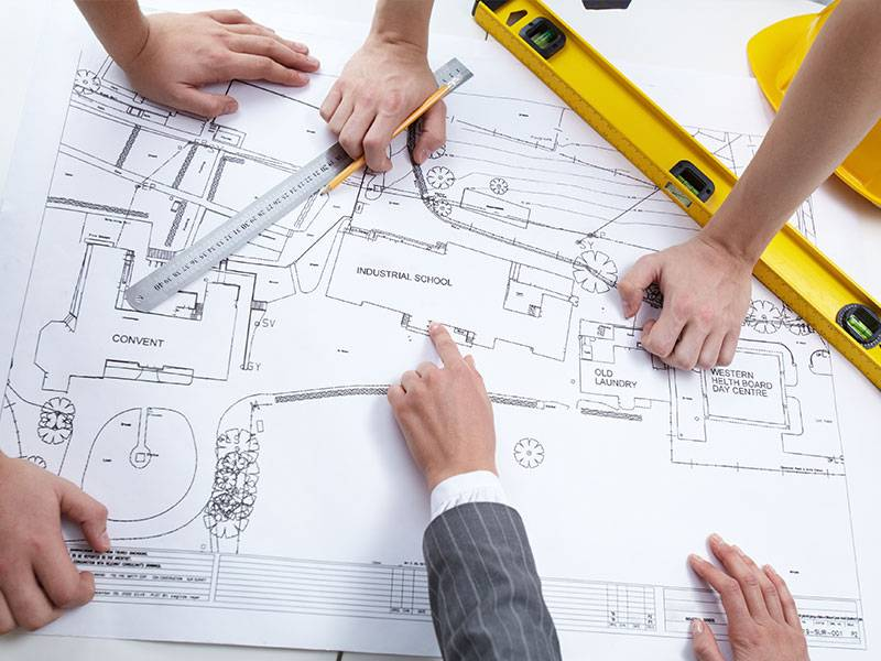 A photo of an architect working on an initial design plan of a community area along with the designers.