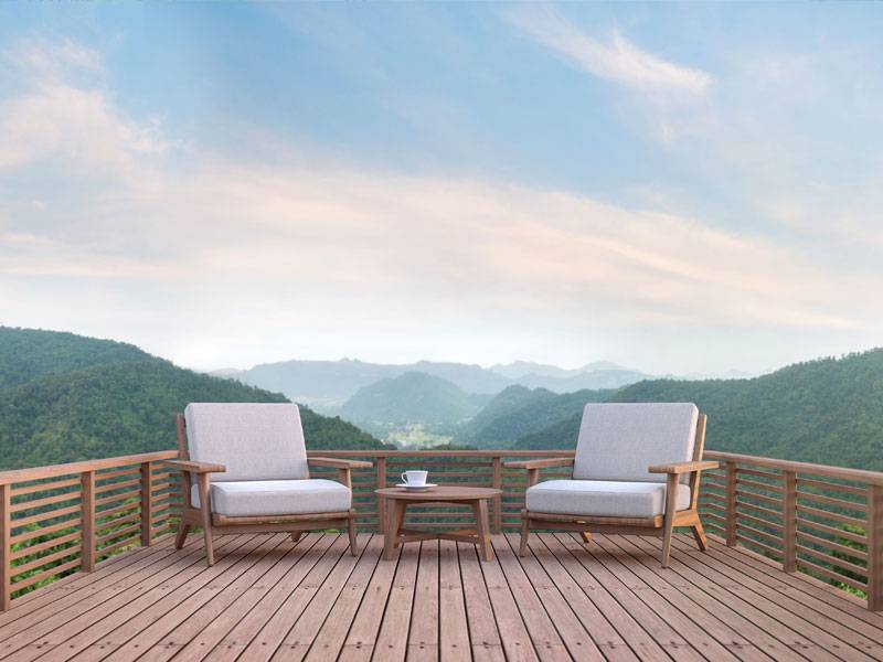 Red oak wooden deck with matching railing and furniture overlooking a green mountain range in California